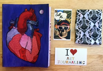 A handmade junk journal with an anatomical heart on the cover next to stickers I made, ready to send to someone