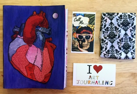 A handmade junk journal with an anatomical heart on the cover next to stickers