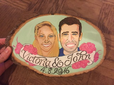 A painted portrait of a couple on a wood block as a wedding gift, created with ink and acrylic paint.