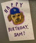 A birthday card I made for a friend with a drawing of her Dachshund wearing a LA Dodgers baseball hat, I created the card with acrylic markers and ink.